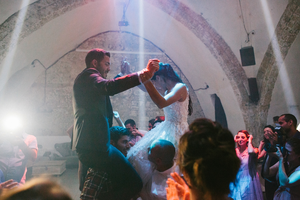Couple lifted on guests shoulders for dancing - Hamam Wedding Tel Aviv Jaffa Israel - Sigala Photography