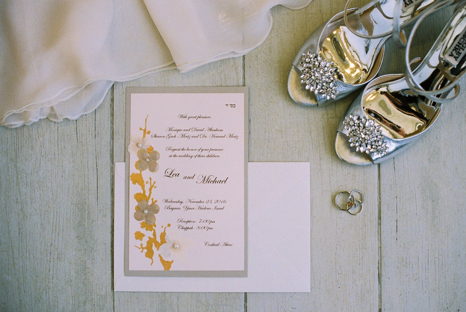 Styled wedding details - invitation, rings, and Badgley Mischka shoes