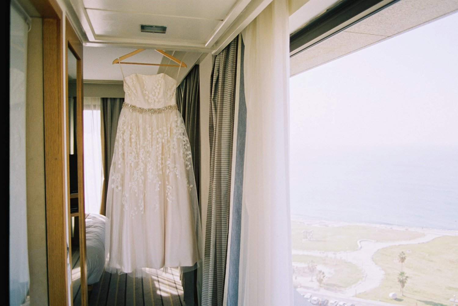 Wedding dress hanging in David InterContinental Hotel overlooking Tel Aviv coastline