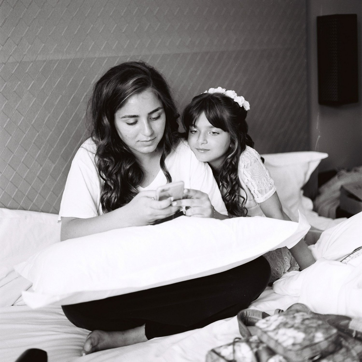 sisters of the bride sitting on bed while getting ready for wedding