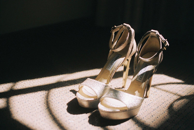 bride's pair of Jimmy Choo wedding shoes in window light