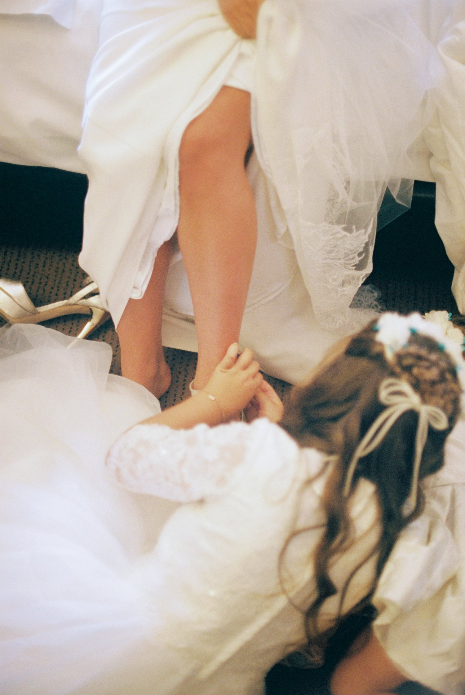 little sister helping bride put on her shoes before wedding