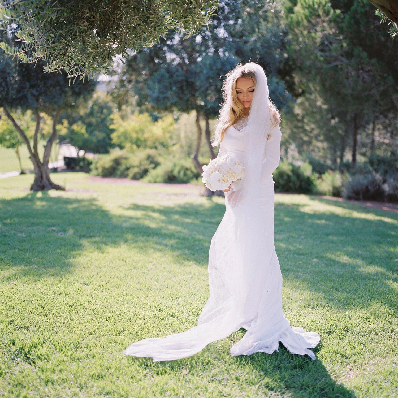 portrait of bride holding bouquet by ADAYA before wedding at Olmaya Jerusalem