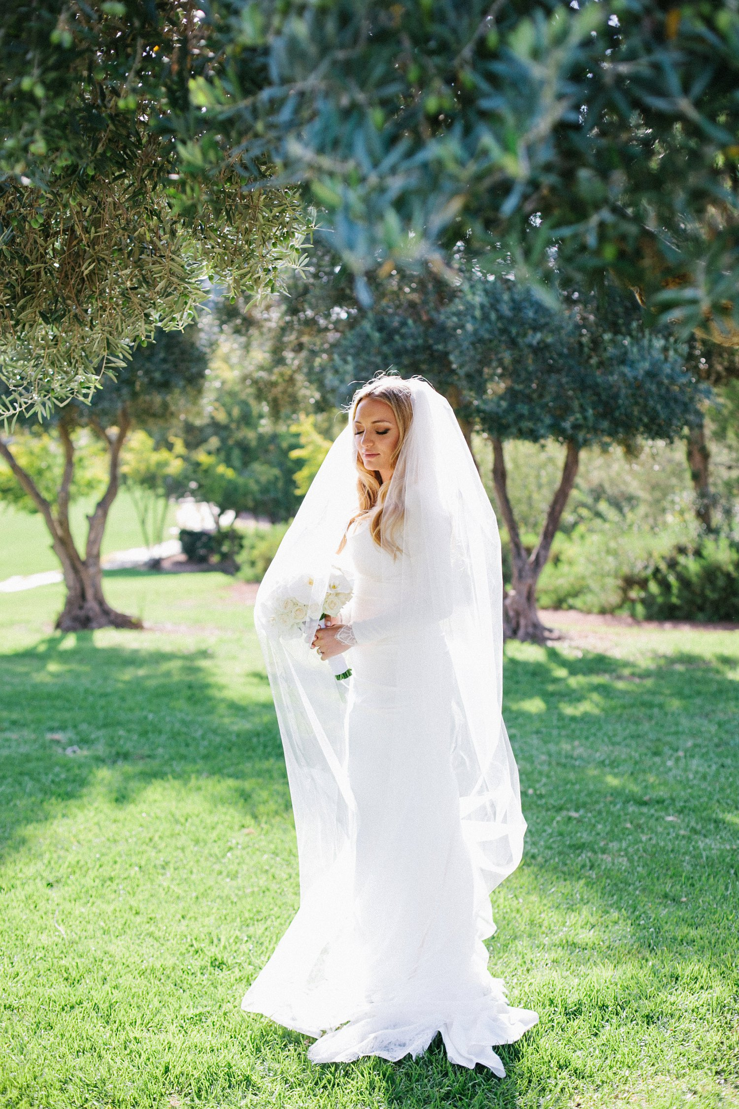 portrait of bride holding bouquet surrounded by olive trees before wedding at Olmaya Jerusalem