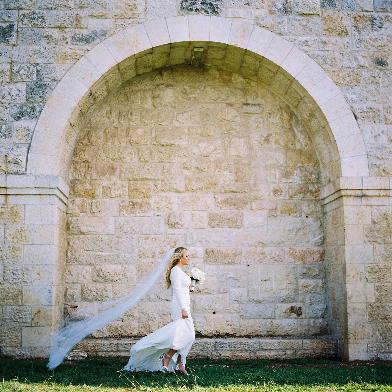 bride walking past stone arch at Haas Promenade Jerusalem