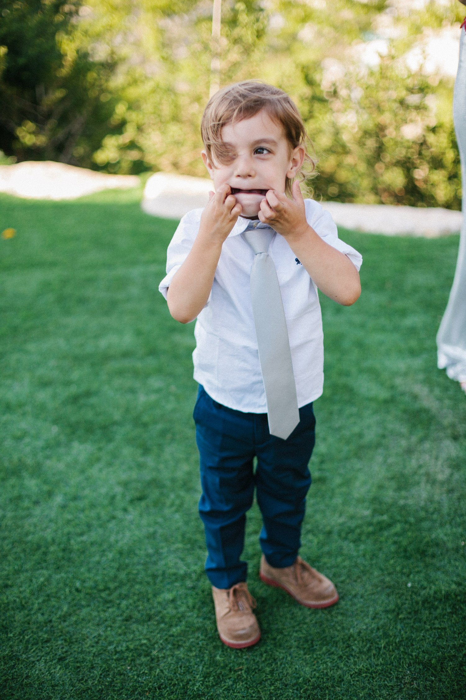groom's nephew making silly face during portraits at Olmaya wedding