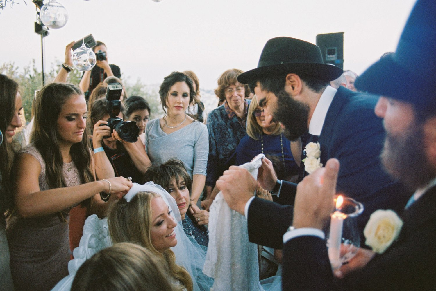 groom putting veil on bride while surrounded by family and friends during Olmaya wedding