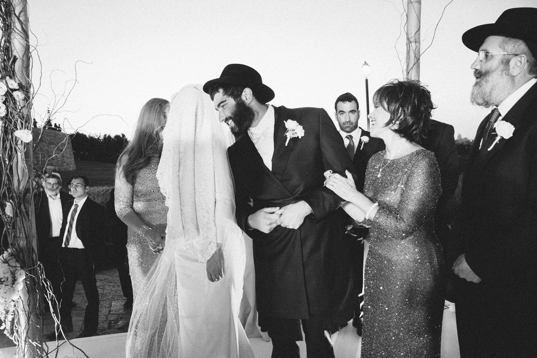 groom smiling as bride circles him under chuppah