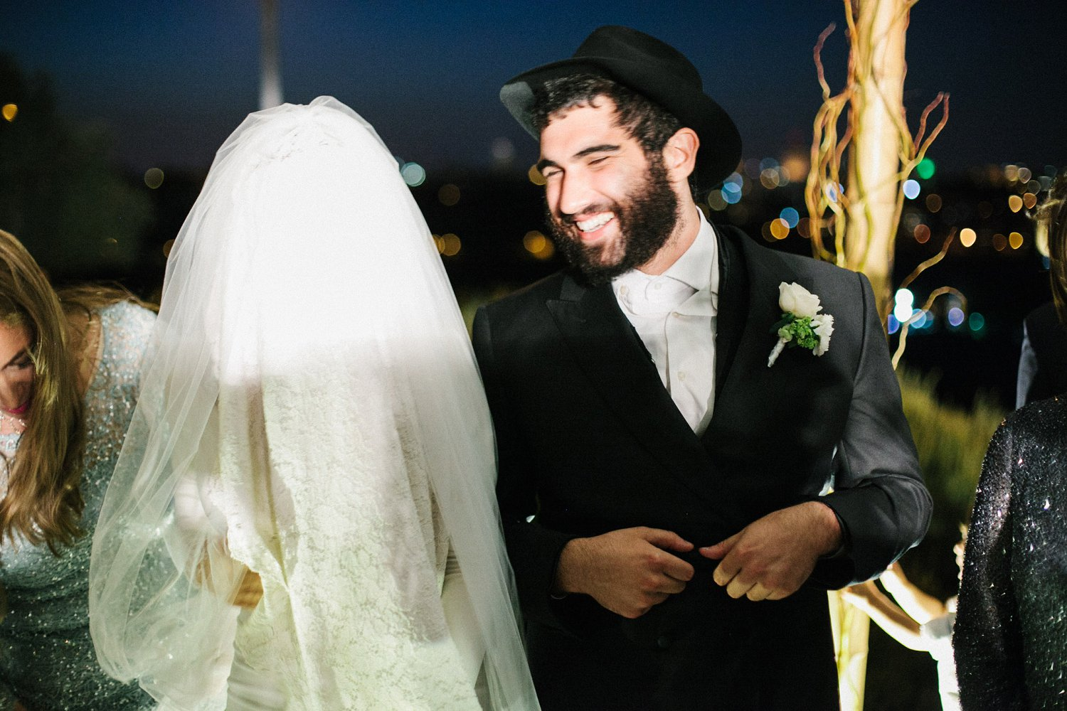 bride and groom laughing while standing under chuppah