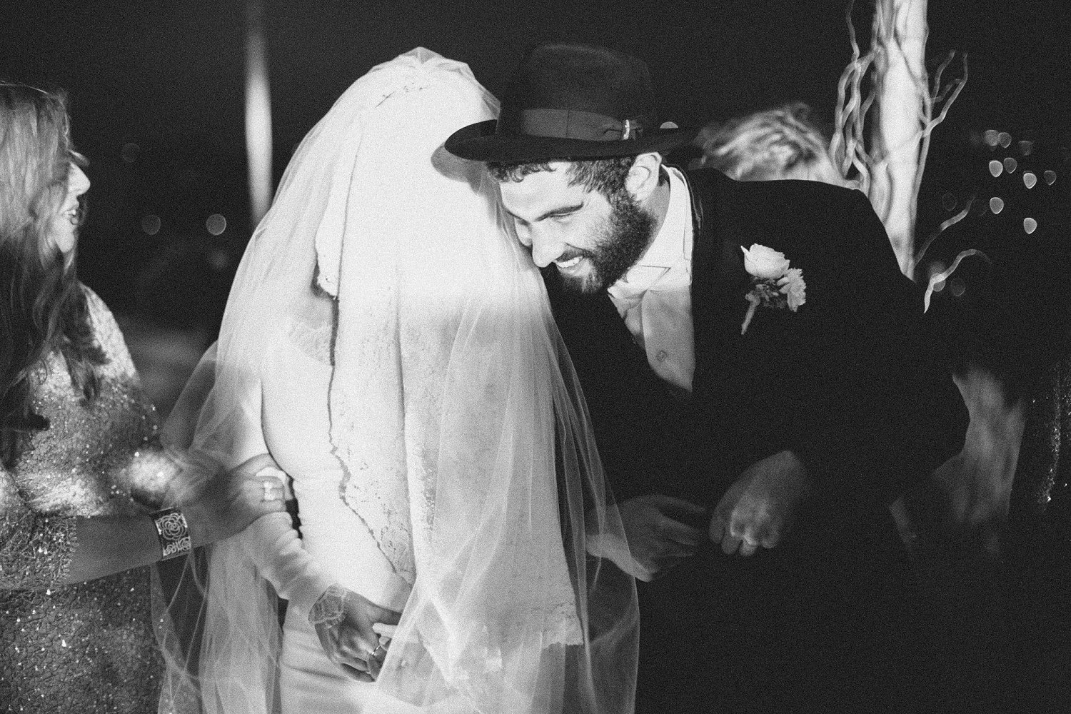 bride talking to groom while standing under chuppah during wedding ceremony