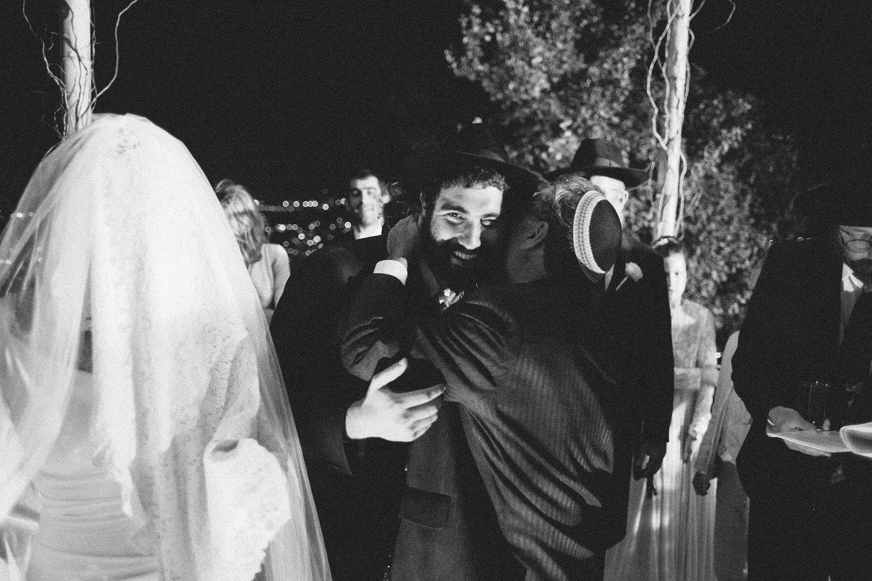 guest hugging groom under the chuppah at Olmaya