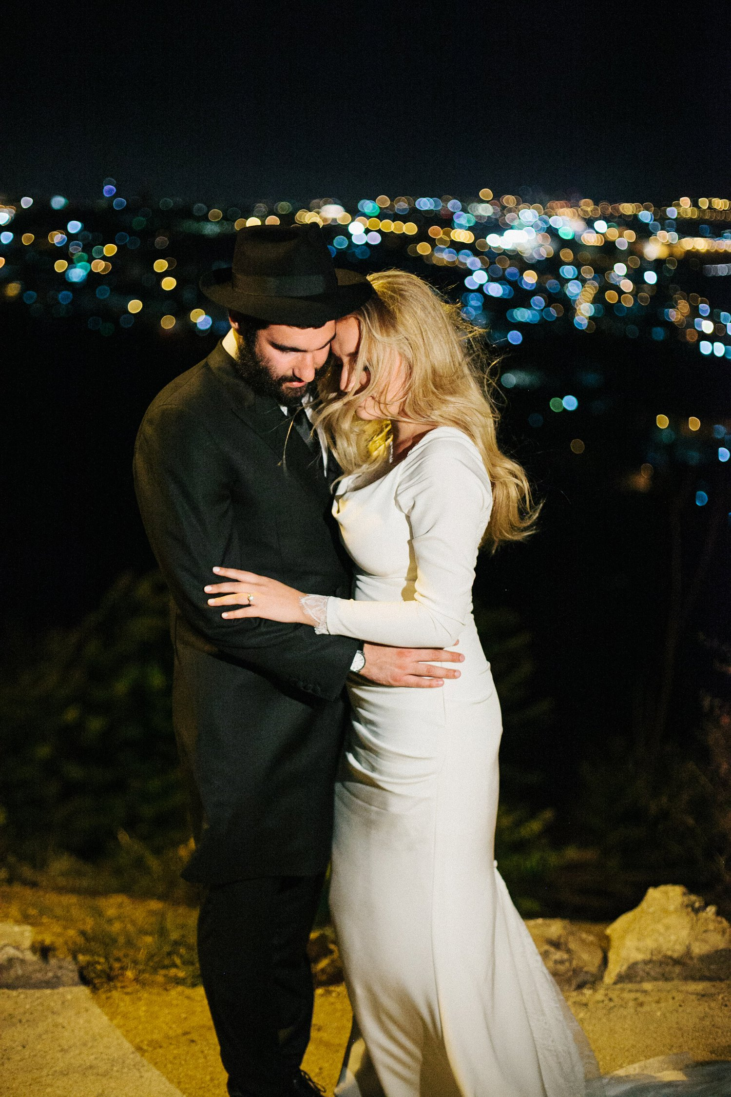 portrait of bride and groom embracing with lights of Jerusalem in the background