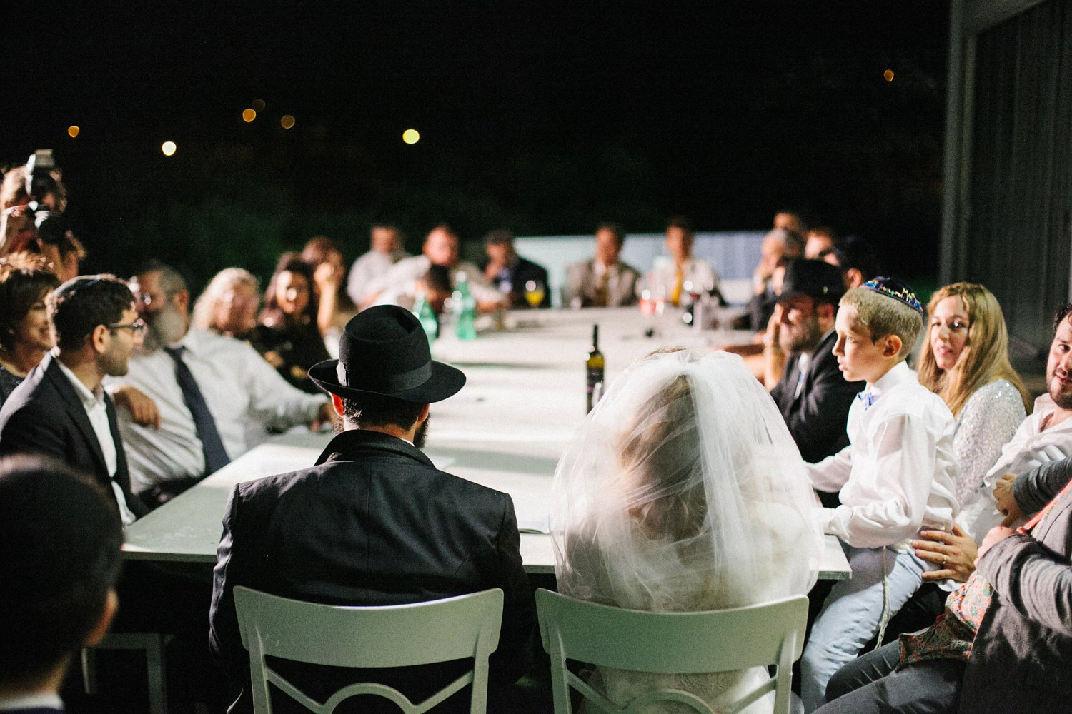 bride and groom sitting during sheva brachot at the end of Olmaya wedding