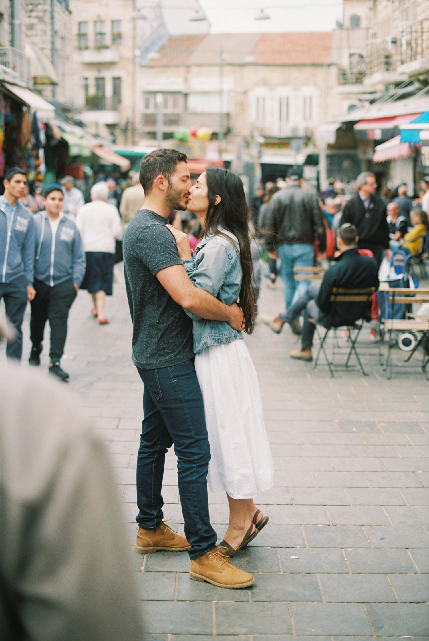 Couple kissing in the Machane Yehuda market in Jerusalem Israel during their engagement session