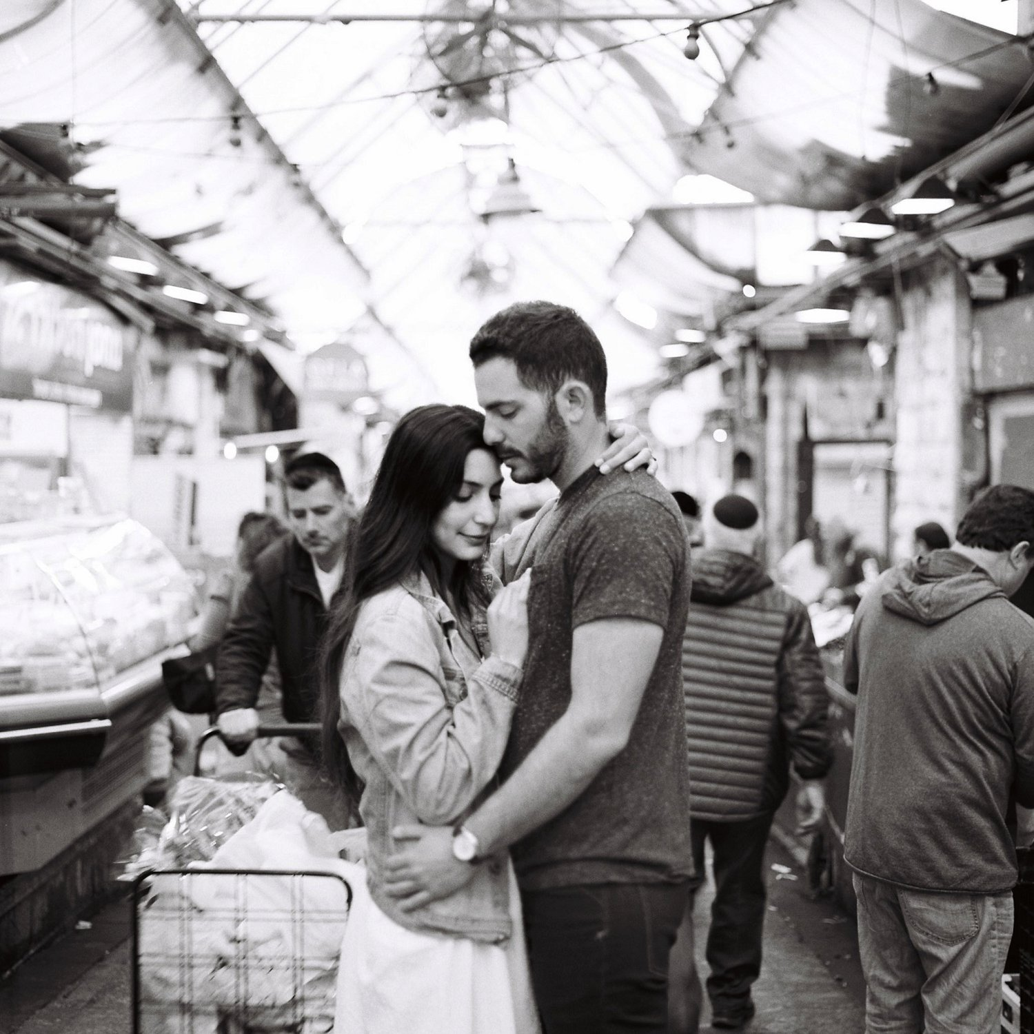 Couple embracing in the Machane Yehuda market in Jerusalem Israel during their engagement session