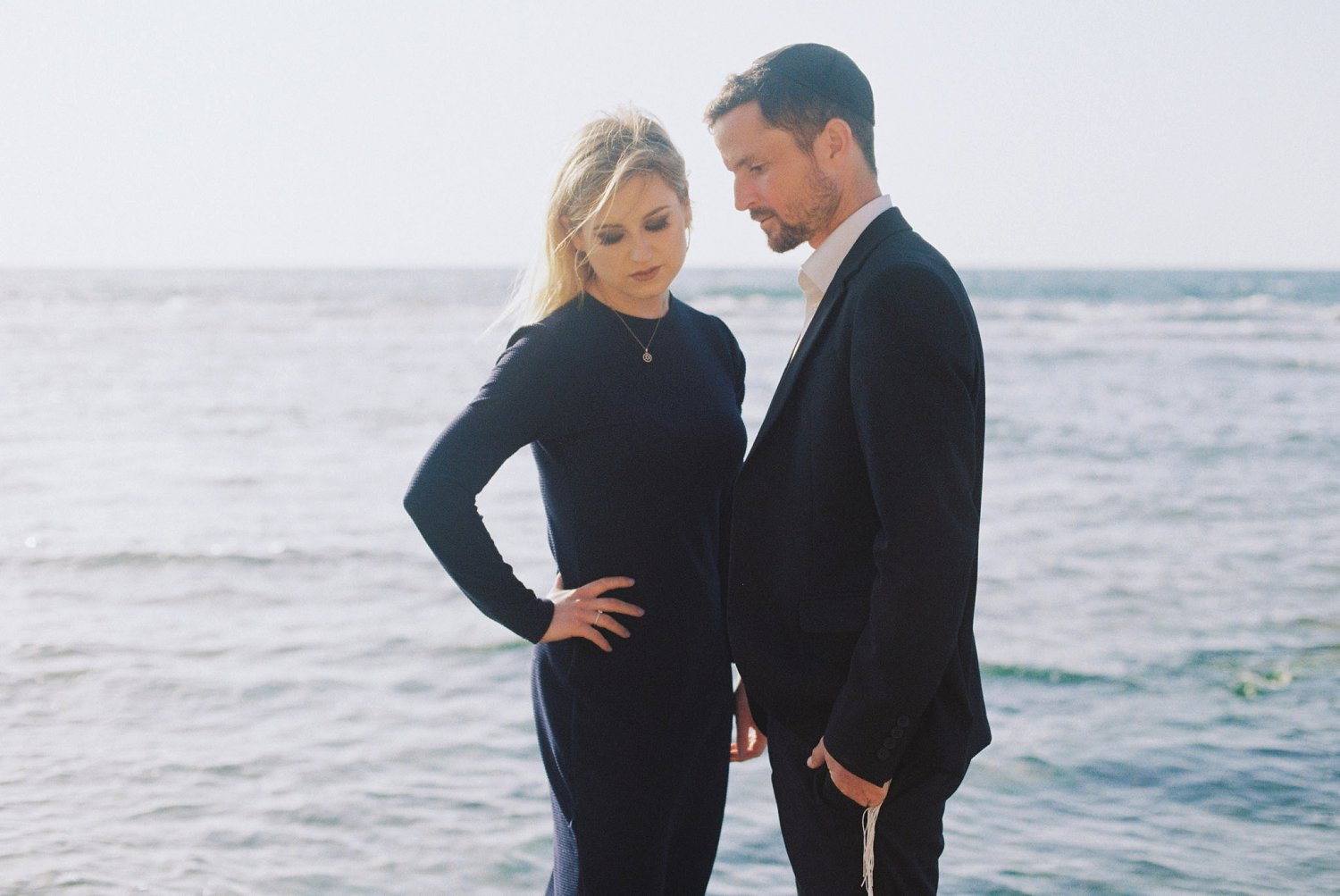 Couple standing against the sea during their Palmachim Beach engagement session