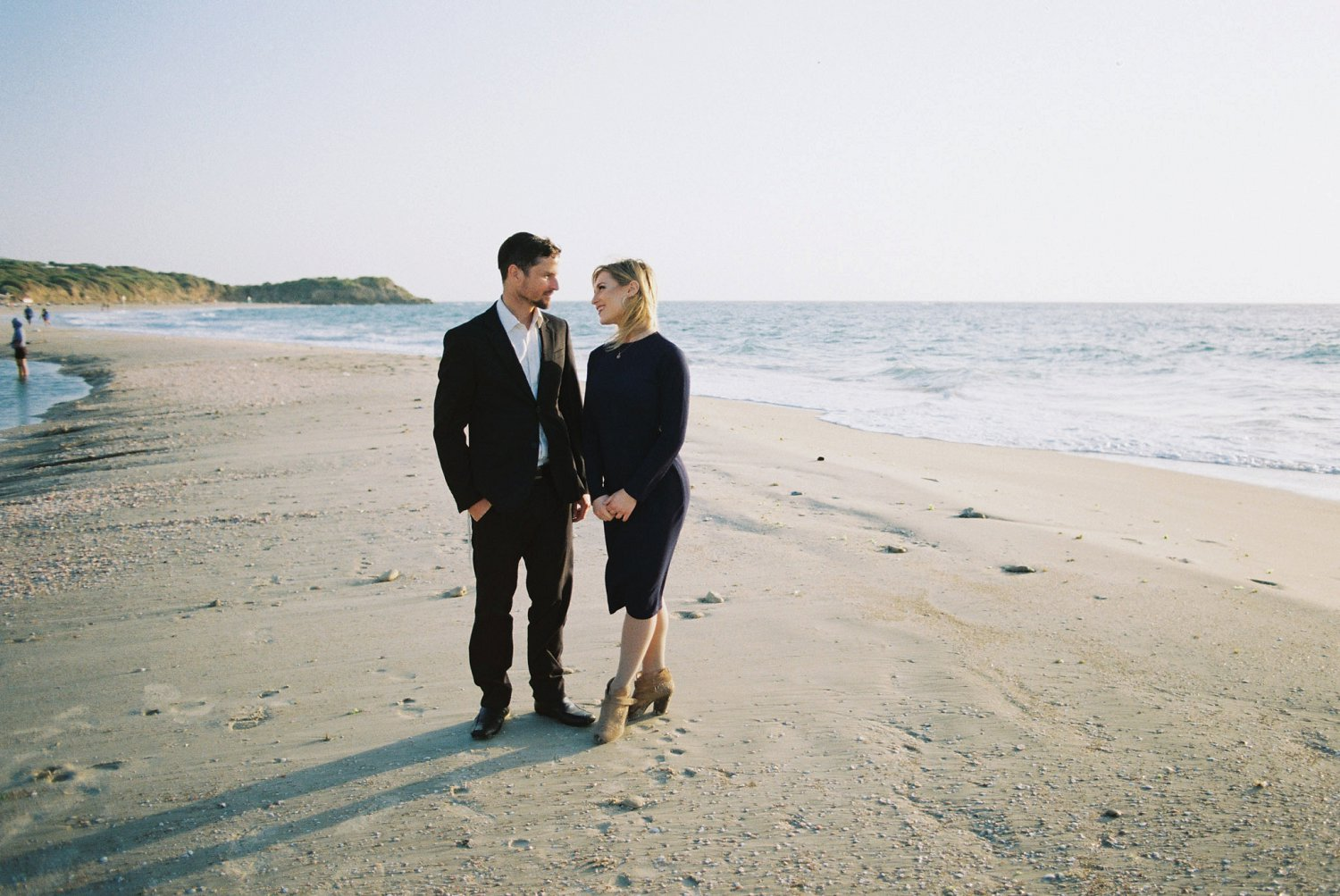 Couple looking at each other while standing on a sandbar during their Palmachim Beach engagement session