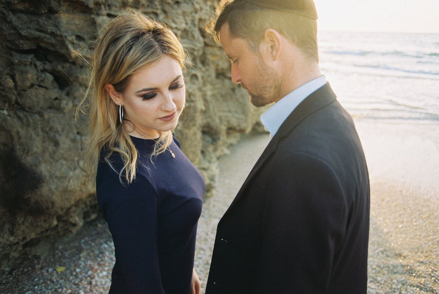 Couple standing between the cliffs and sea during their Palmachim Beach engagement session