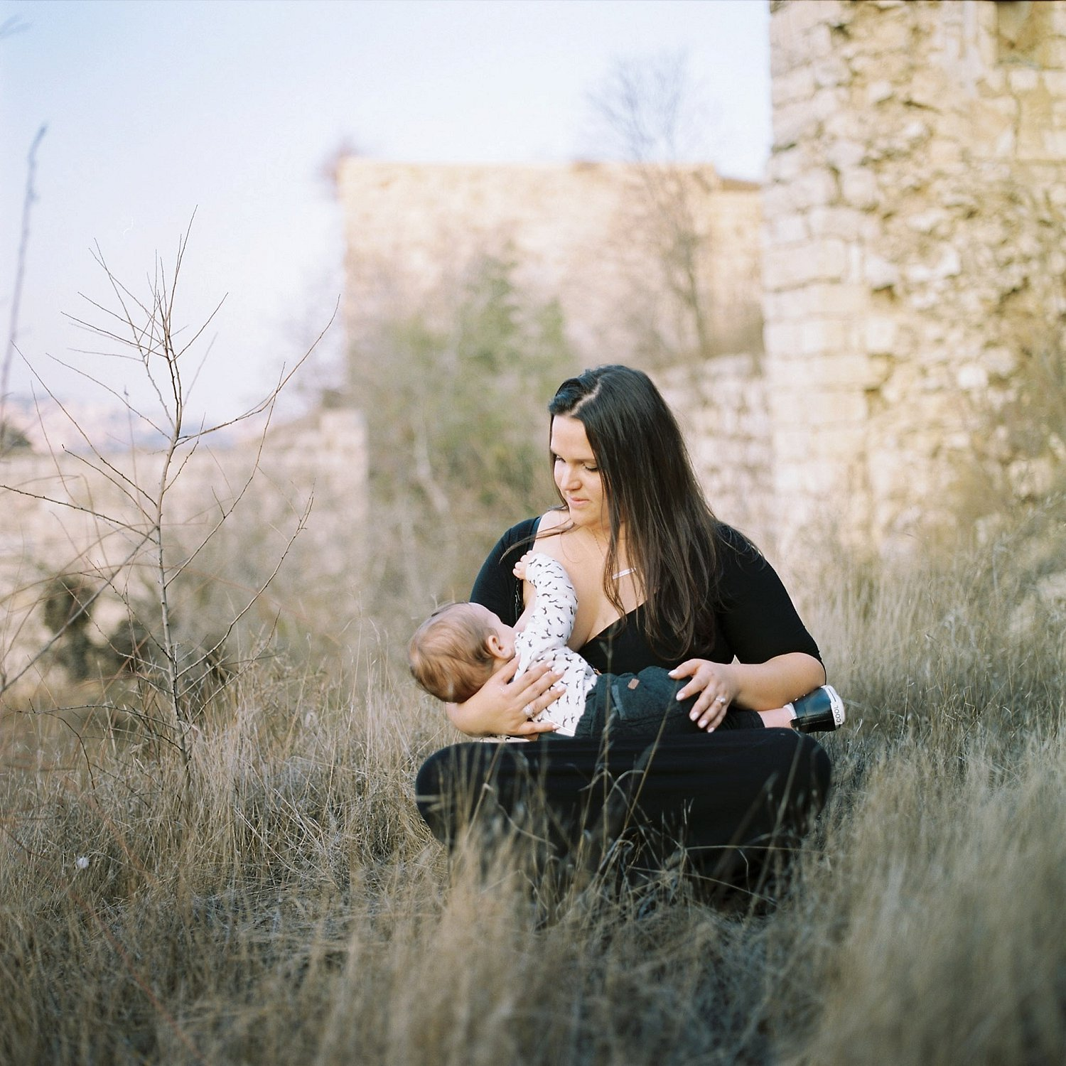 Image of mother nursing her son while sitting amongst the Lifta ruins
