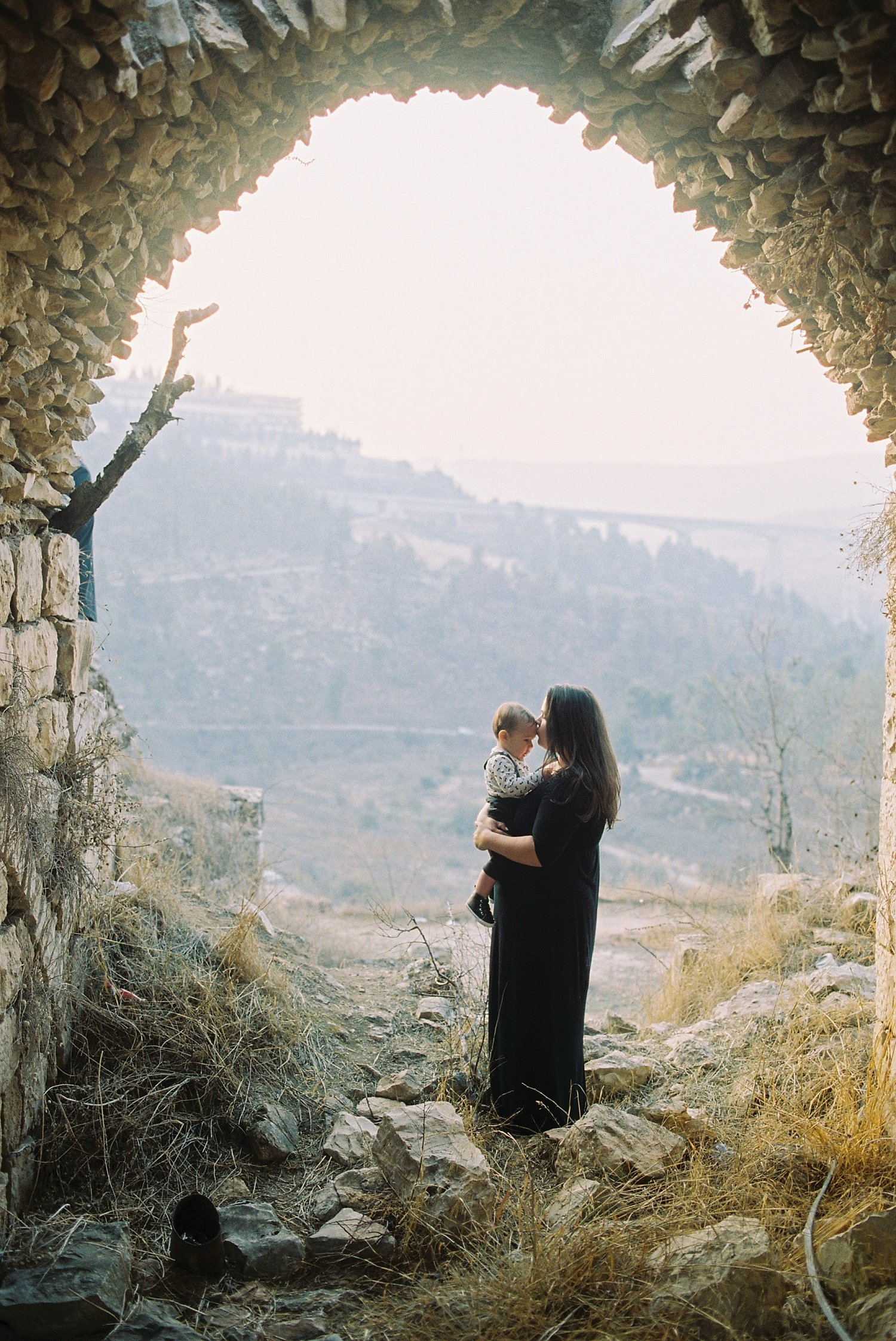 Mother and son standing under an archway in Lifta Ruins Jersusalem