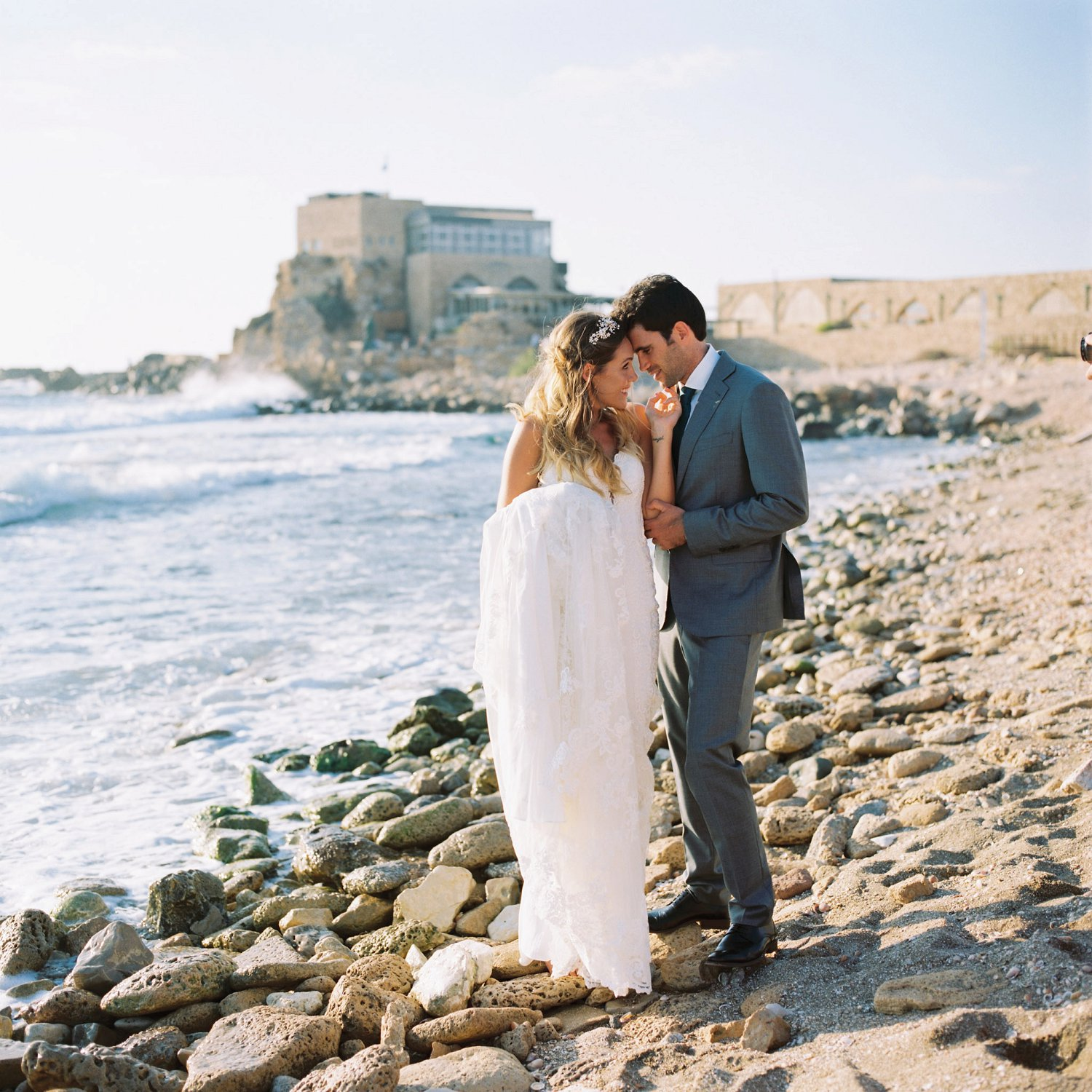 Portrait of bride and groom on beach in Caesarea Harbor