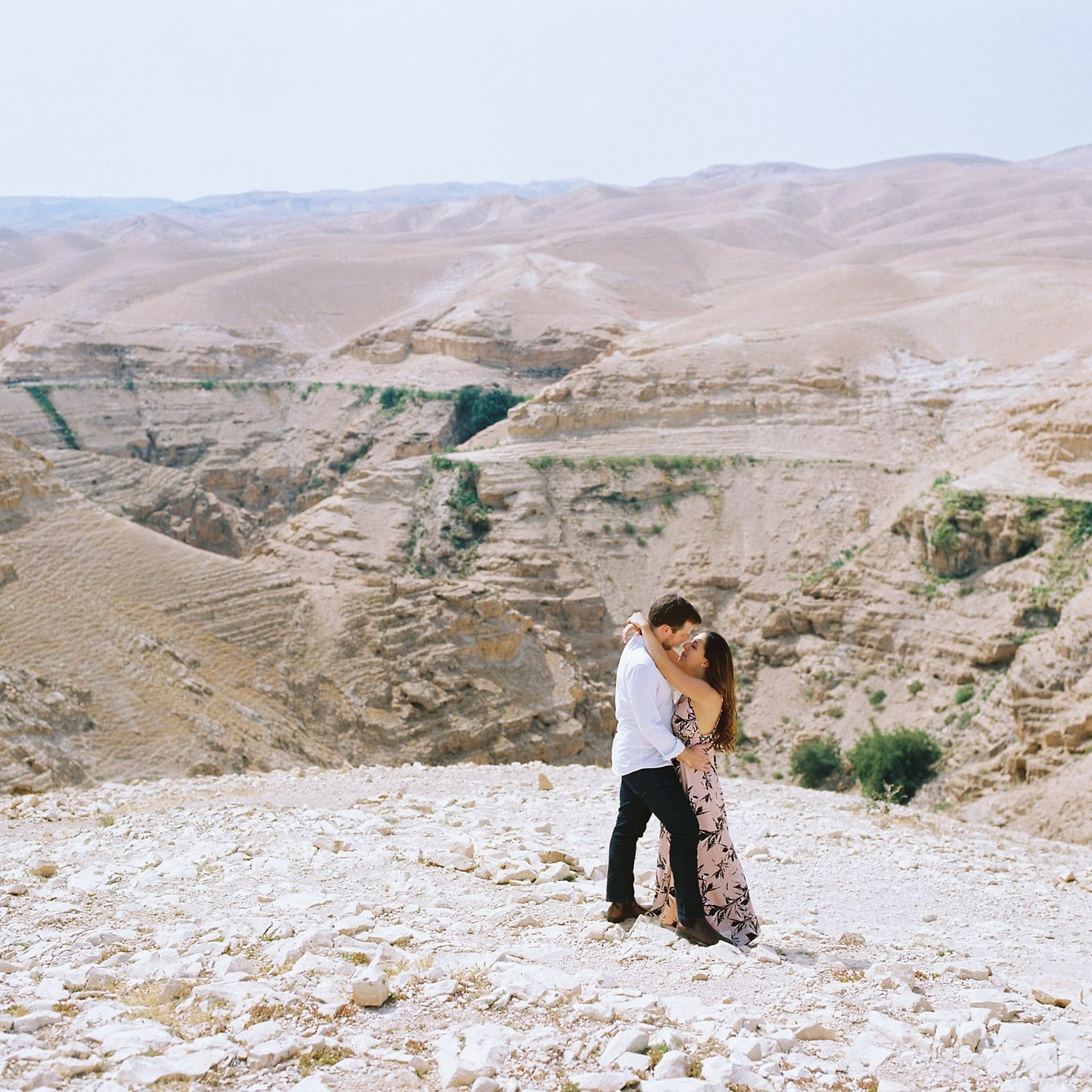 Couple holding each other overlooking canyon in Judean desert engagement session