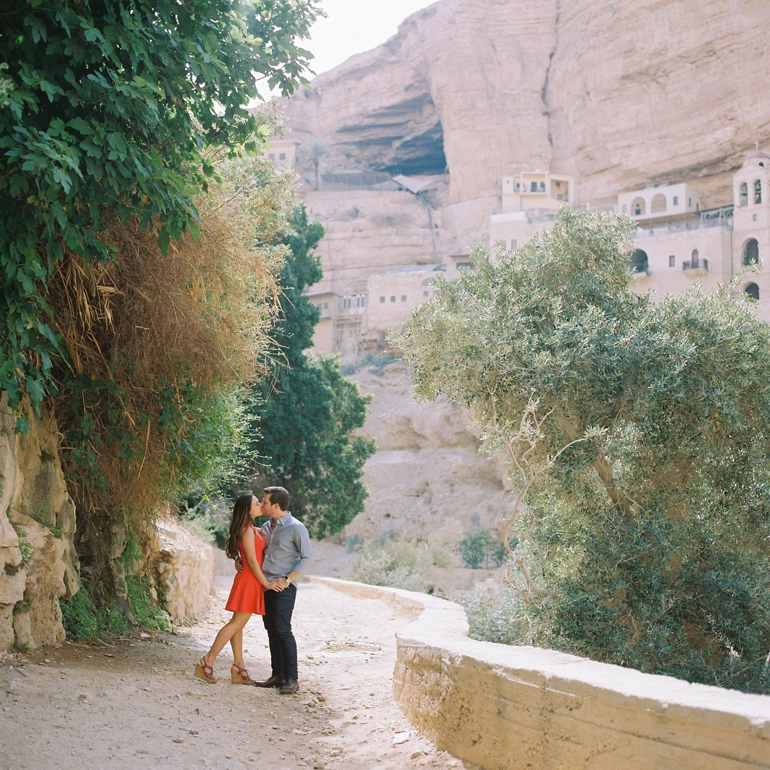 Couple kissing with St. George Monastery in background during Judean desert engagement